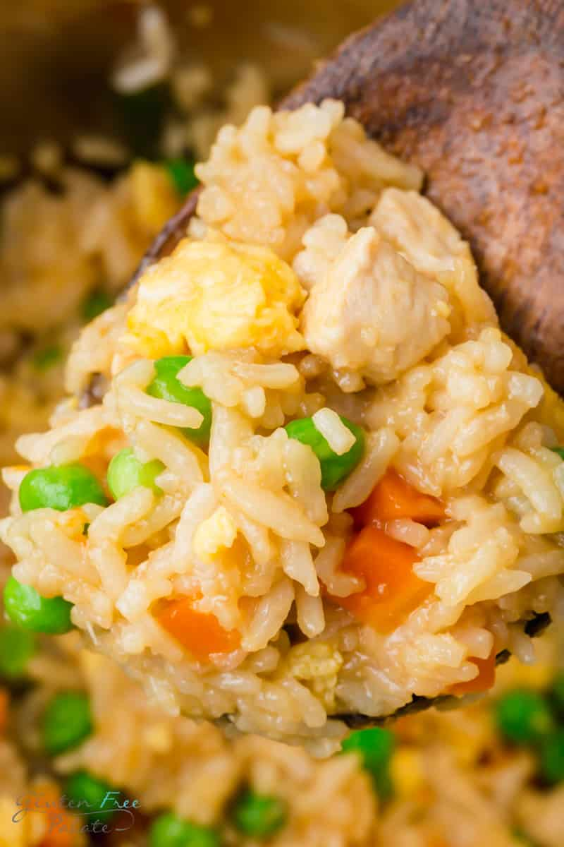 closeup of a wooden spoon holding chicken fried rice