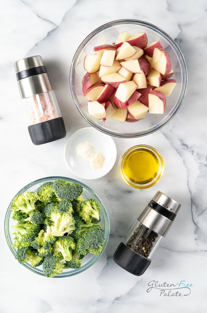 ingredients needed for roasted potatoes and broccoli in separate bowls on a marble counter.