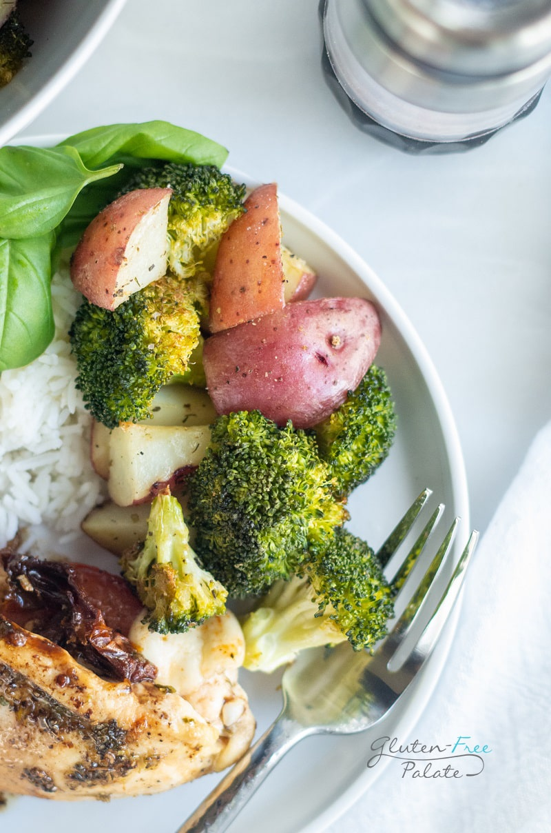 a plate of chicken, rice, spinach, potatoes and broccoli with a fork on the edge.