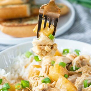 Shredded Hawaiian chicken with pineapple and green onions mixed with rice, being eaten with a fork.