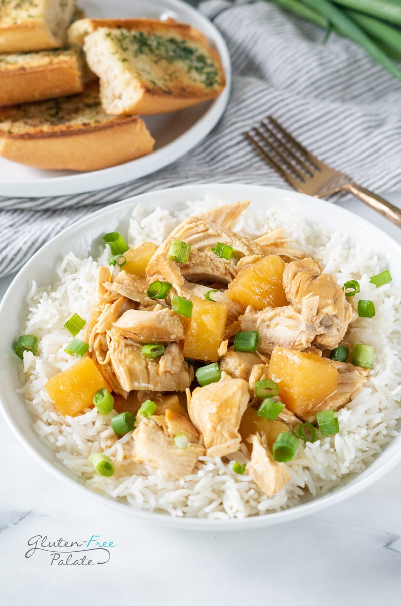 crockpot cooked chicken with pineapple on a bowl of rice, topped with scallions
