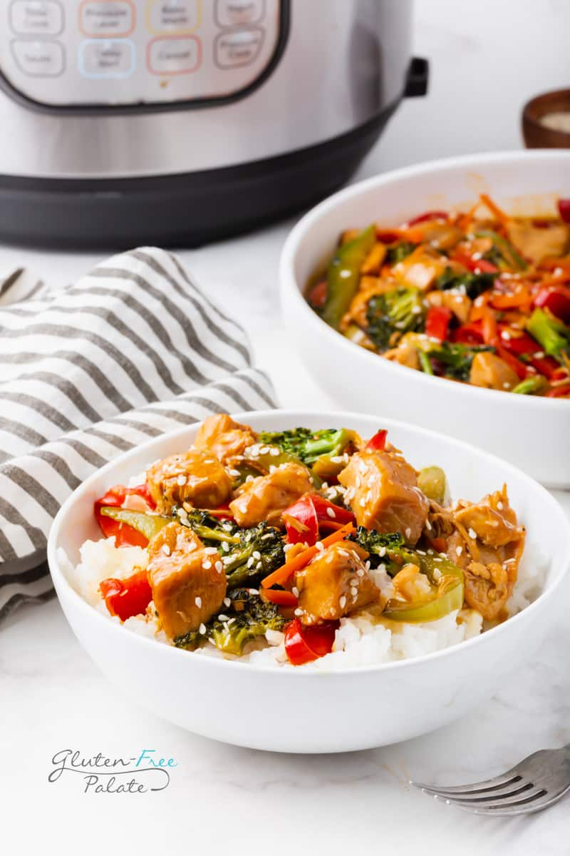 a white bowl of rice topped with chicken stir fry. Behind that is a serving bowl of the stiry fry and an instant pot.