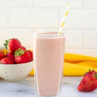 a tall glass filled with strawberry banana peanut butter smoothie, with a yellow and white striped straw. In the background is a bowl of strawberries and a yellow towel.
