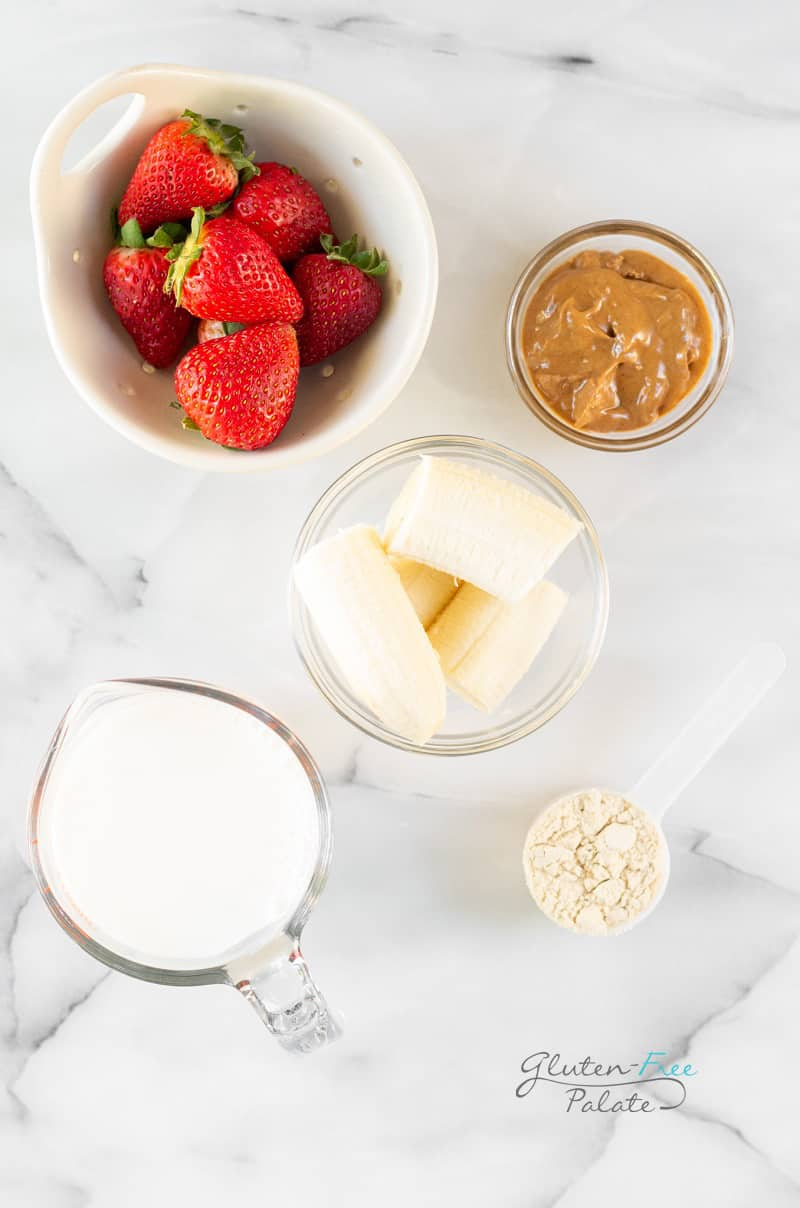 Ingredients for strawberry banana peanut butter smoothie, all in separate bowls on a marble counter.