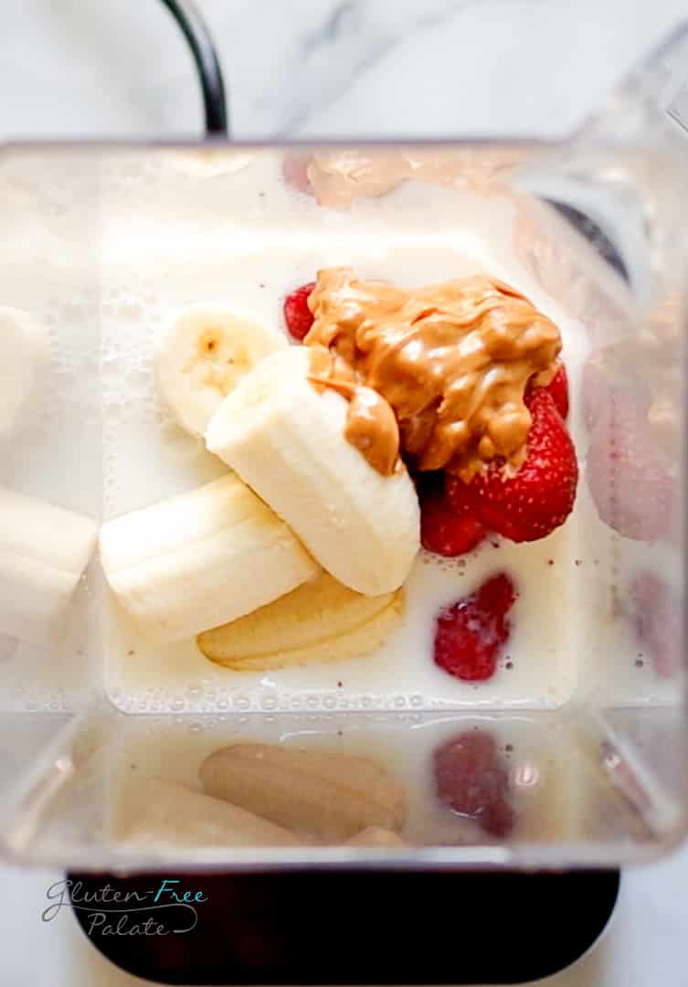 Top down view of a blender filled with milk, bananas, peanut butter, and strawberries.