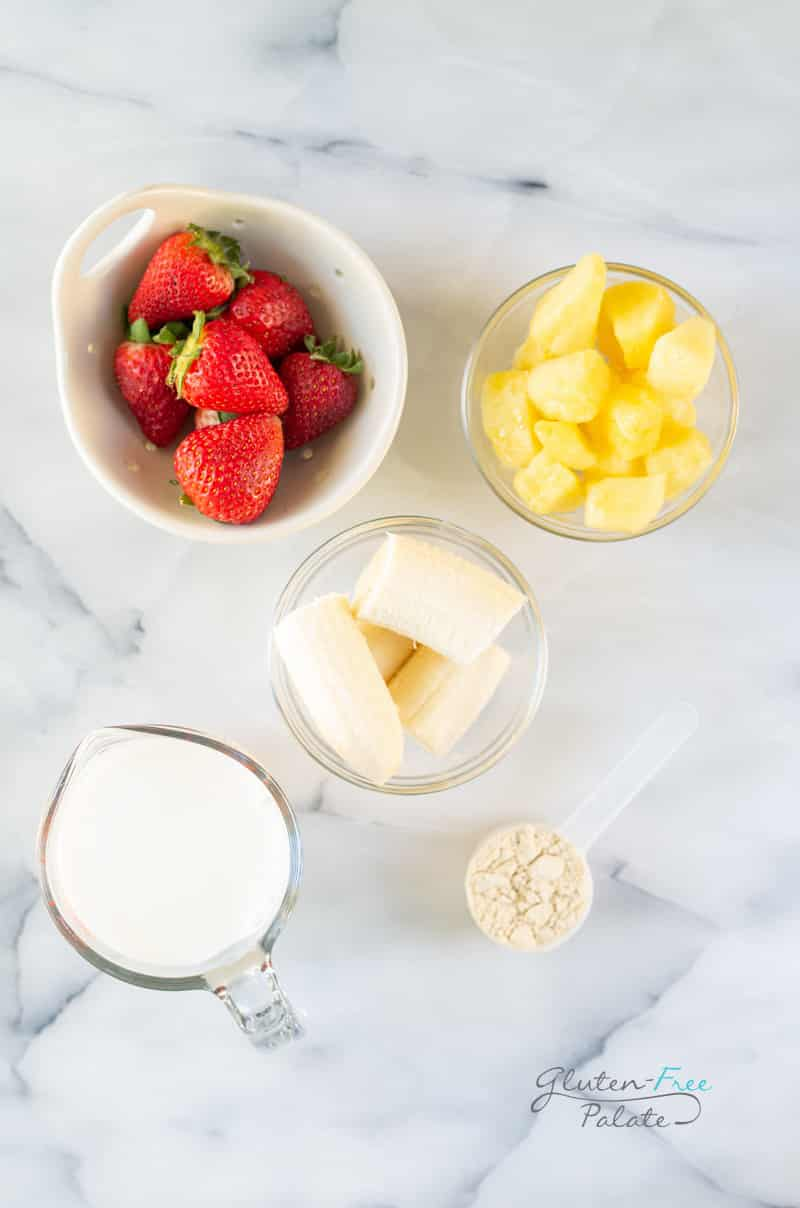 Ingredients for strawberry banana pineapple smoothie, all in separate bowls on a marble counter.