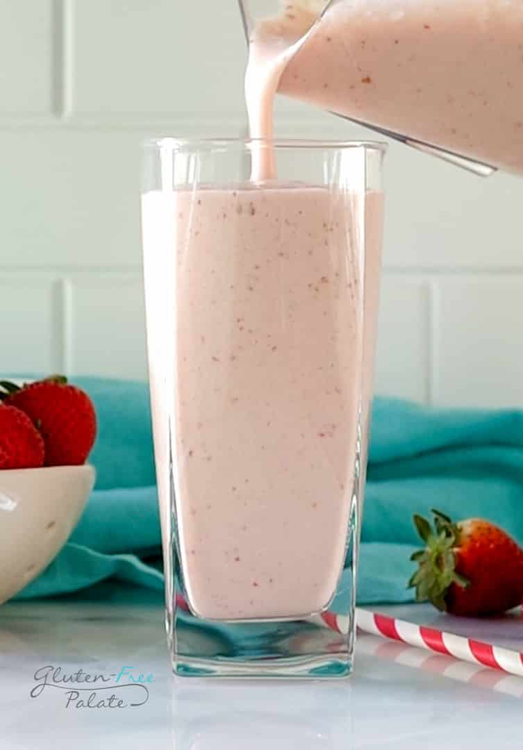 A tall glass being filled with strawberry banana pineapple smoothie from a pitcher. In the background is a bowl of strawberries and a teal kitchen towel.