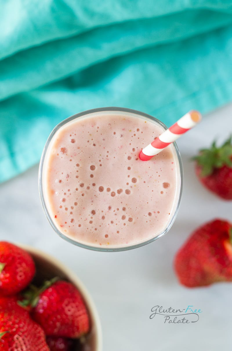 Top down view of a tall glass filled with strawberry banana pineapple smoothie with a red and white striped straw. In the background is a bowl of strawberries and a teal kitchen towel.