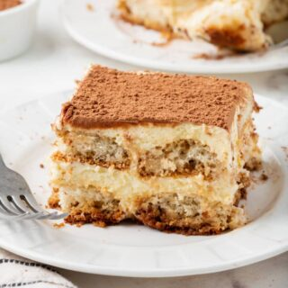 a white p late with a square piece of tiramisu on it.