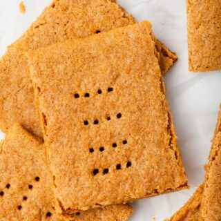 rustic looking homemade rectangular graham crackers piled on a marble counter.