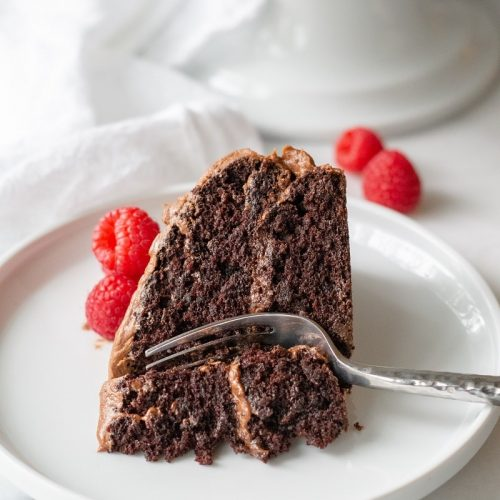 slice of gluten-free chocolate cake with chocolate frosting and raspberries