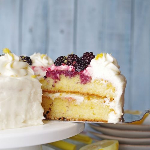 a close up of a serving spoon serving a slice of gluten-free lemon cake topped with white frosting and blackberries